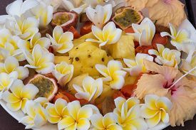 foto of papaya fruit  - Fruit dessert salad with pineapple papaya passion fruit and white frangipani flower on the plate - JPG