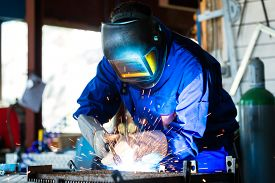 picture of welding  - Welder bonding metal with welding device in workshop - JPG