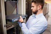 Technician removing server from rack mounted server in server room poster
