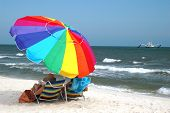 foto of summer beach  - Beach scene with beach chairs and umbrella with shrimp boat in water.