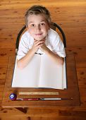 Child At Desk With Open Book