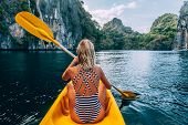 Woman paddling a kayak in the island lagoon between mountains. Kayaking in El Nido, Palawan, Philipp poster