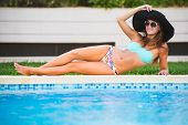 Beautiful Tanned Sexy Girl In Bikini And Black Hat Posing At A Swimming Pool poster