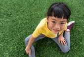 Little Asian Girl With Sweat On Face, Looking At Camera. Sitting On Grass, Overhead Shot. poster