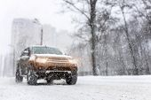 Heavy Snowfall And Blurred Suv Awd Car On Road. 4wd Vehicle On City Street At Winter. Seasonal Roads poster
