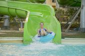 Beautiful Girl Riding A Water Slide. Happy Woman Going Down On The Rubber Ring By The Orange Slide I poster