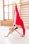 Young flexible acrobat in activewear exercising with resistance band on the floor poster
