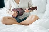Asian Girl Play The Guitar From The Morning Wake Up. Making It Feel Bright And Soothing Music Can De poster