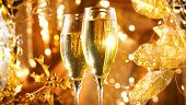 Holiday Champagne over Golden glow background. Christmas and New Year celebration. Two Flutes with S poster