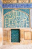 Tiled oriental ornaments Ateegh Jame mosque's wall with window , Esfahan, Iran