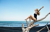 Young  Happy Girl In Swimsuit Sitting On Old Tree Snag Rise Hands High In Air, Posing On Black Sand  poster