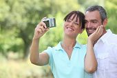 Couple in countryside taking photos