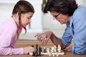 Young girl playing chess with grandma