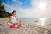 Woman Working On Her Laptop On A Beautiful Beach
