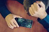 Desperate And Astonished Man Holds Cracked Smartphone . Screen Broken Smartphone. Cracked Phone Brok poster