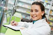 cheerful smiling pharmacist chemist woman standing in pharmacy drugstore