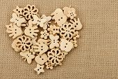 Vintage wooden buttons arranged in heart shape on handwoven cotton fabric.