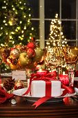 Festive dinner table setting with red ribbon gift