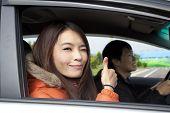 Feliz pareja sonriente conducir en el coche con el pulgar hacia arriba