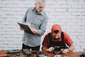 Old Manager Checking Motherboard Near Worker. Worker With Tools. Computer Hardware. Young And Old Wo poster