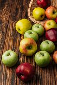Scattered Multicolored Apples And Wicker Basket On Wooden Table poster