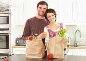 stock photo of grocery-shopping  - Young Couple Unpacking Shopping In Modern Kitchen - JPG