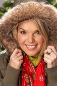 Fashionable Woman Wearing Parka Coat And Scarf In Studio In Front Of Christmas Tree