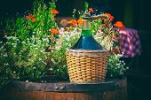 Large Vintage Wine Bottles In Wicker Basket On A Barrel. Autumn Still Life With A Bottle Of Wine And poster