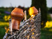 Clay Pot And Jug Hanging On A Wicker Wooden Fence poster