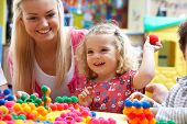 foto of daycare  - Young woman playing with girl - JPG