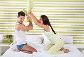 young affectionate couple fighting pillows