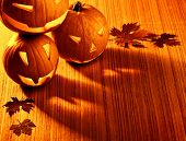 Picture of halloween glowing pumpkins border, three orange carved pumpkins and old dry leaves on woo