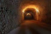 stock photo of grotto  - Well lit catacombs of the castle in Dubno Ukraine - JPG