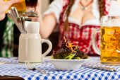 Young people in traditional Bavarian Tracht eating in restaurant or pub lunch or dinner, focus on sa
