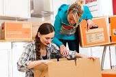 Young women - presumably friends - with moving box in her house moving in or out of a apartment, focus on moving box
