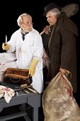 stock photo of jekyll  - Evil doctor brandishing cleaver exchanges glances with grave robber over bloody corpse - JPG