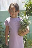 stock photo of youg  - Pretty youg filipino girl holding a pineapple. ** Note: Slight blurriness, best at smaller sizes - JPG