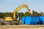 stock photo of dumpster  - yellow demolition bulldozer beside a blue dumpster - JPG