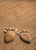 pair trace feet made of a pebble stone on the sea sand desert texture backdrop