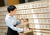 Woman searches something in card catalog composed of set of wood boxes at the library. Education