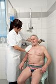 a senior is bathed by nurses