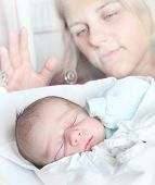 Newborn baby boy sleeping in a incubator. His mother looking at. Close up with shallow DOF.