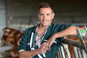 Portrait of smiling herdsman standing in barn