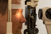 image of slit  - Patient or customer at slit lamp at optometrist or optician - JPG