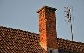 picture of chimney  - Orange roof tiles chimney and old analog TV antenna - JPG