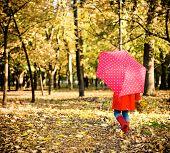 Little Girl With Polka Dots Umbrella Walking Through Alley