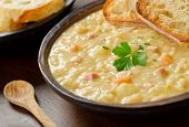 image of pea  - A rustic bowl of hearty spit pea soup with smoked ham carrots potato and french bread - JPG