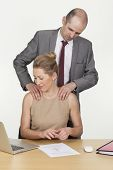 stock photo of groping  - Harassment in the workplace as a randy male boss stands behind a female colleague groping her shoulders with his hands - JPG