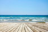 The tropical blue ocean coast with waves over wide wooden floor of planks and logs background