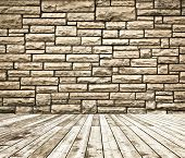 Background of aged grungy textured brown brick and stone wall with light wooden floor with whiteboar